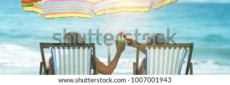 Cute mature couple lying on deckchairs at beach