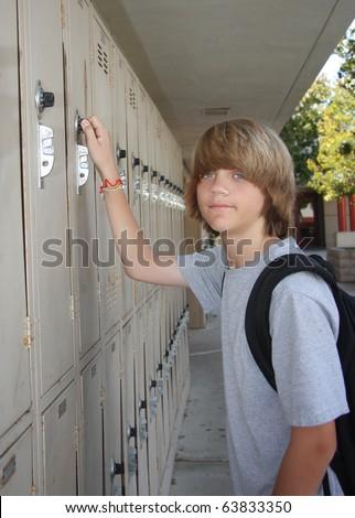 Cute middle school teen opening his school locker. - stock photo