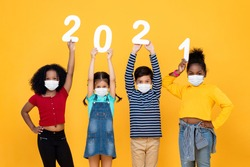 Cute mixed race children wearing medical face masks holding 2021 numbers isolated on yellow background, new year in time of pandemic concepts