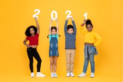 Cute mixed race kids smiling and holding 2021 numbers isolated on yellow background for new year concepts