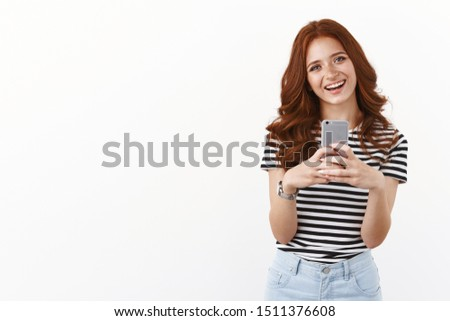 Cute modern millennial girl with red curly hairstyle, tilt head joyfully, smiling enthusiastic, holding smartphone, taking selfie in mirror, making goofy grin, messaging friends, white background