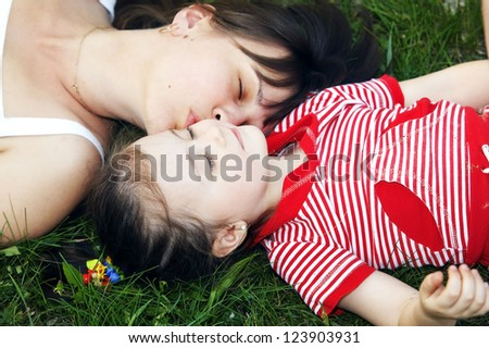 Cute mom and daughter relaxing on the lawn