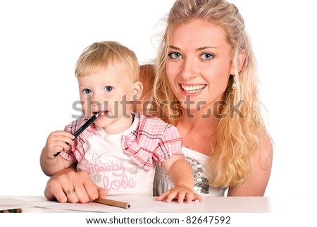 cute mom with her daughter drawing at the table
