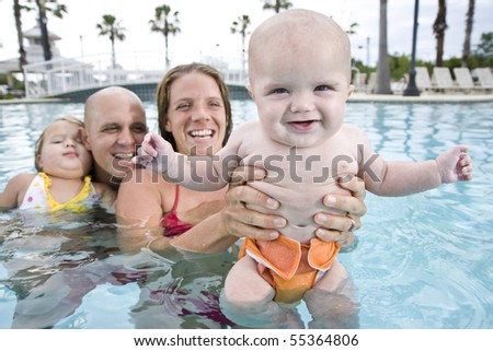 Cute 6 month old baby with family smiling in swimming pool