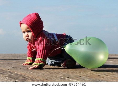 cute 10-month old baby with green balloon