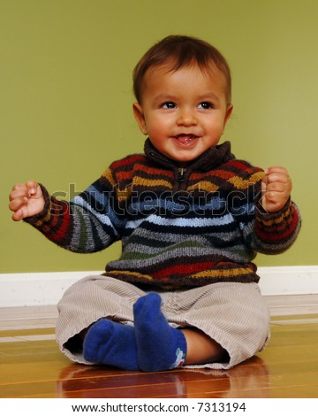 Cute 6-9 month old biracial boy happily sitting on a shiny hardwood floor.