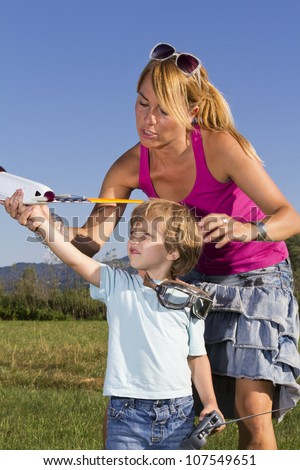 Cute mother demonstrating her young son how to launch RC plane