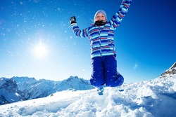 Cute motion action portrait of young ski girl jump in mid-air and throw snow up over blue sky