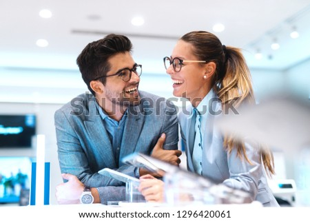 Cute multicultural couple in formal wear smiling and looking for new tablet to buy. Tech store interior.
