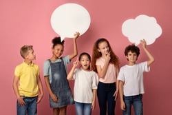 Cute multinational schoolchildren with empty speech bubbles on pink background, space for design