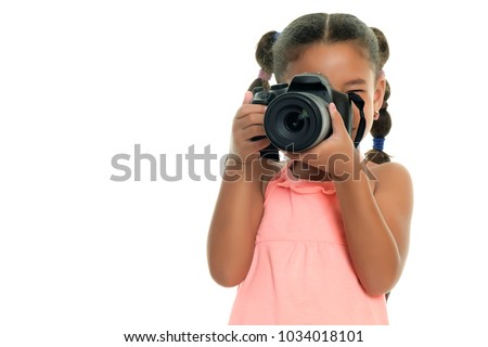 Cute multiracial small girl taking pictures with a professional camera - Isolated on a white background