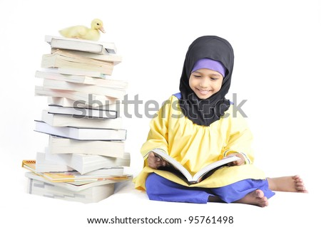 Cute Muslim girl reading book in isolated white background.
