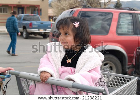Cute Native American girl sitting in a shopping cart ready for grocery store run with her mother