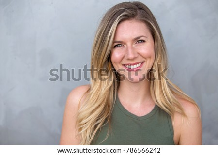 Cute natural blonde woman smiling with perfect white teeth and glowing skin