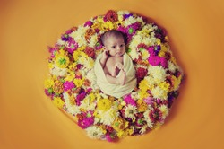 cute new born baby girl lying in sunflower, marigold, roses and other colorful flower wreath, wrapped in white cloth, on yellow orange background isolated photoshoot