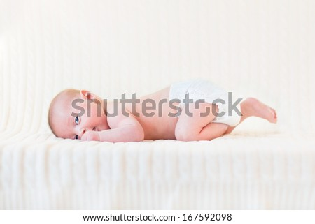 Cute newborn baby boy relaxing on a white knitted blanket