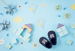 Cute newborn baby boy shoes with festive decoration over blue background. Baby shower, birthday, invitation or greeting card idea