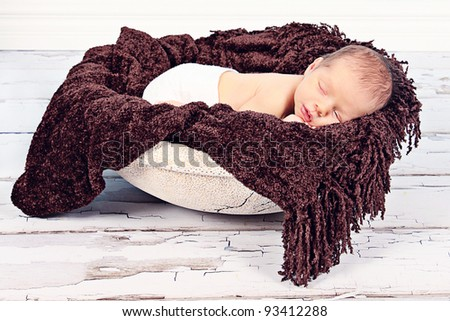 Cute newborn baby boy sleeping in Bowl with blanket