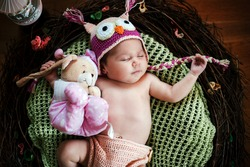 Cute newborn baby girl with knitted owl hat is sleeping in a braches nest.