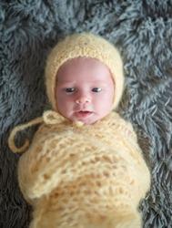 Cute newborn baby in a yellow hat