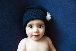 Cute newborn baby in the  dark blue hat. Happy baby on a  dark blue background. Closeup portrait of newborn baby. Baby goods packing template. Nursery. Medical and healthy concept. Christmas. New Year