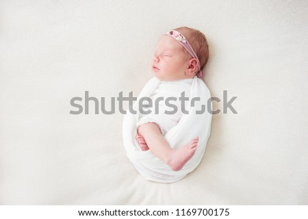 Cute newborn baby lies swaddled in a white blanket. Copy space and top view
