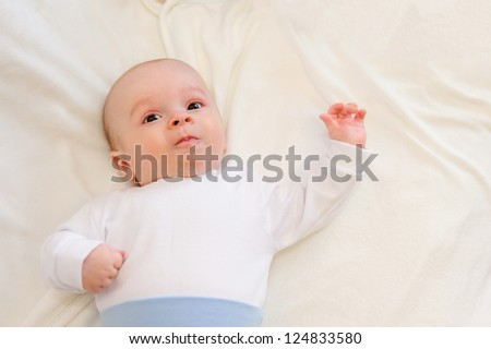 Cute newborn baby lying in bed on blanket
