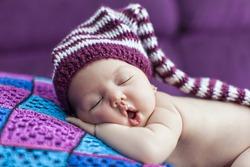 Cute newborn baby sleeps in a hat