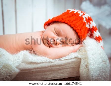 Cute newborn baby sleeps in a santa claus hat close-up