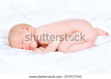 Cute newborn baby sleeps peacefully on a soft white blanket.