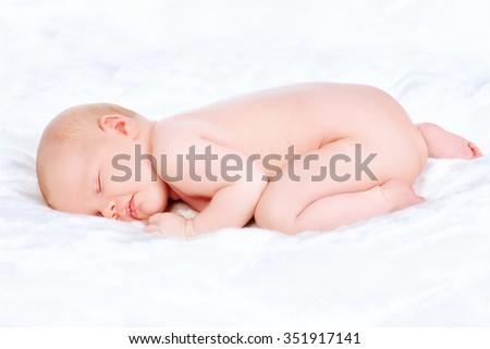 Cute newborn baby sleeps peacefully on a soft white blanket.