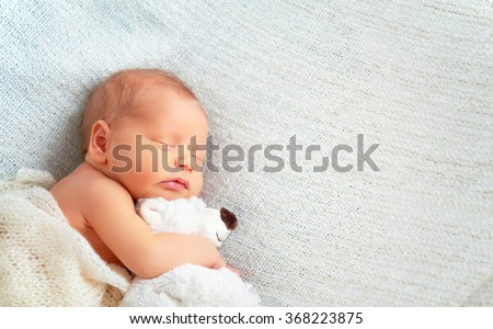 Cute newborn baby sleeps with a toy teddy bear white #368223875