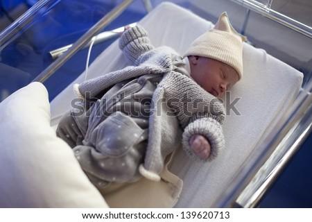 Cute newborn in nursery at the hospital