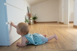 Cute newborn touching closed wardrobe and lying on belly on wooden floor with barefoot. Side view of adorable red-haired infant trying to crawl at home. Childhood and infancy concept