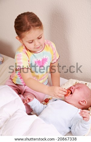 Cute older sister with crying newborn in bed