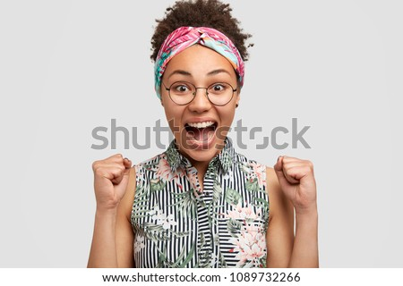 Cute overjoyed female clenches fists with great happiness, wears stylish headband and blouse, happy to recieve salary. Young woman student rejoices getting scholarship, isolated on white background