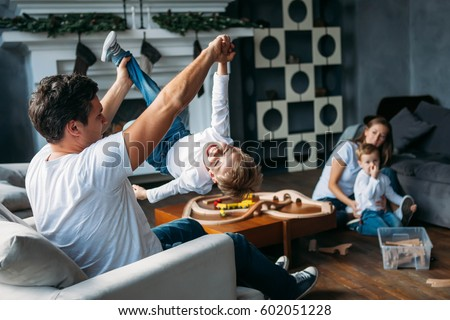 cute parents play with their sons on the floor together indoor #602051228
