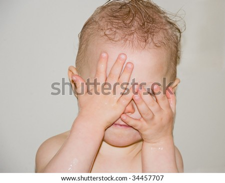 Cute photo of a Caucasian baby playing peek a boo in the bath by covering her eyes with her hands.