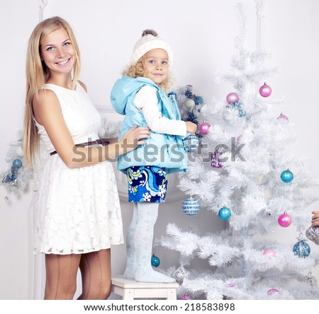 cute photo of little girl with blond curly hair and her pregnant mother decorating Christmas tree