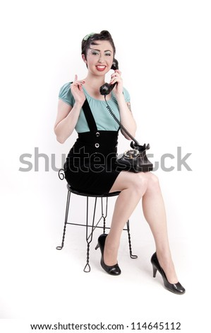 Cute pin up girl talking on an antique telephone