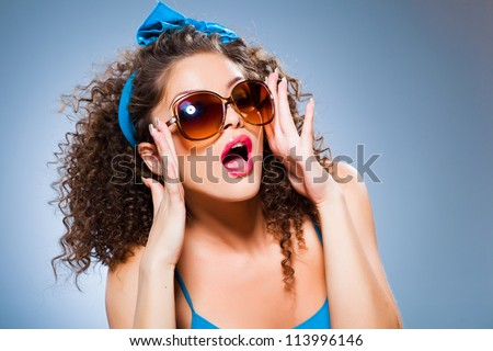 cute pin up girl with curly hair and perfect teeth on blue background - stock photo