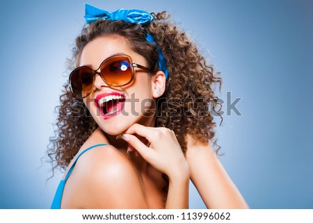 cute pin up girl with perfect teeth smiling, curly hair and sunglasses on blue background