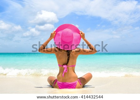 Cute pink bikini beachwear woman relaxing in perfect paradise destination on beach travel vacation. Girl from the back holding fashion straw floppy hat sitting on sand looking a turquoise ocean. #414432544