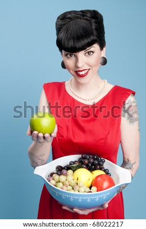 Cute pinup model holding a bowl of fruit