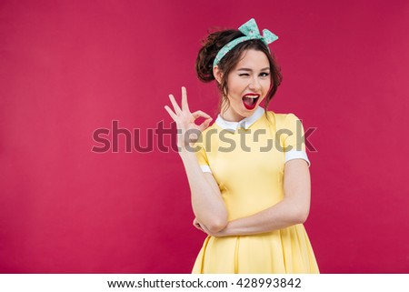 Cute playful pinup girl in yellow dress winking and showing ok sign over pink background #428993842