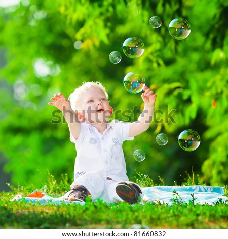 cute playful smiled blond 1.5 years old boy sitting on green grass outdor playing with soap bubbles