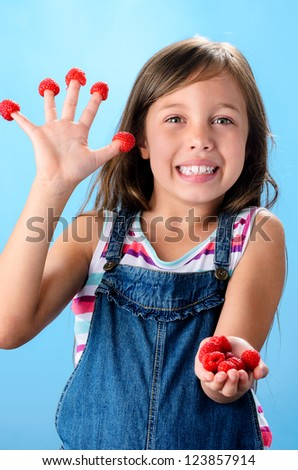 Cute playful young girl with fresh organic raspberries on her fingers and hand, healthy living and diet concept on blue background