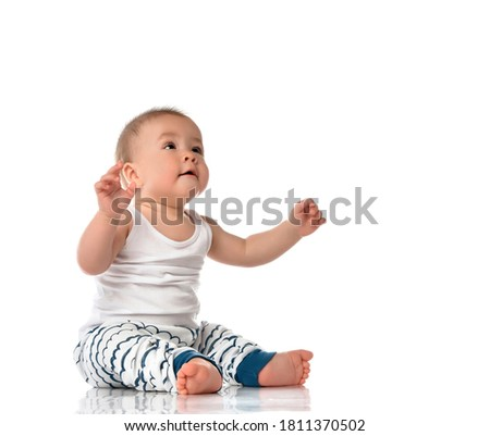 Cute plump barefoot baby boy in night-gown looking up with raised hands sitting on floor. Excited toddler child engaged in game. Kid infant studio portrait on white wall cope space Photo stock ©