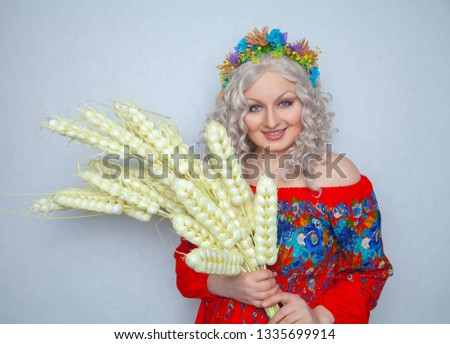 cute plump girl from the village in a red summer sundress with a sheaf of wheat in her hands on white studio solid background