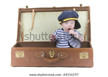 Cute policeman baby sits in suitcase